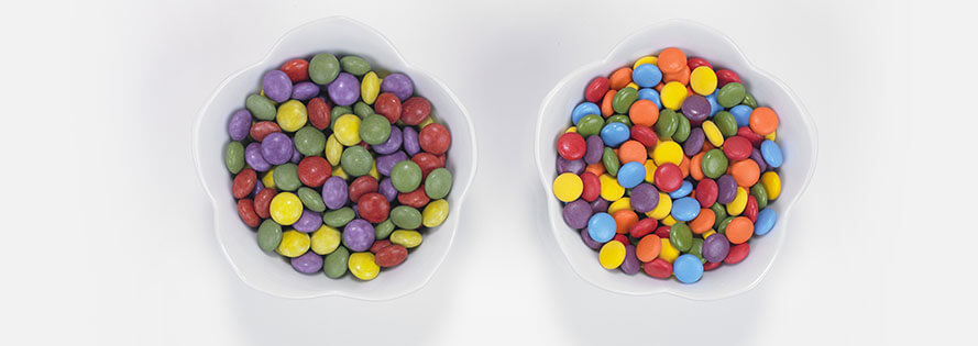 Two adjacent cereal bowls filled with coloful cereal.